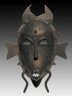 "The kpelie face mask is used in ancestor (kpelie) rituals by the Poro, or Lo, secret sociey of the Senofu peoples. Although mainly worn by men, the kpelie represents female perfection and is used to depict the great mother, the ancestor of all and the giver of life, according to Poro philosophy. The projections at the top of this mask represent the horns of a bull, while the lateral projections at the sides refer to the stylized hair arrangements of Senofu mothers. The ""legs"" at the bottom…"