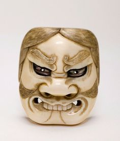 Netsuke. Ivory and mother of pearl. Japan, Meiji Period (1868-1912) HEIGHT 5,2 CM A very expressive netsuke of a demonic no mask of a Buaku with a broad mouth and bare teeth and a large sized nose. (Buaku is a kind of demon with various aspects). Very spirited inlaid eyes of mother of pearl. From the collection of Dr. Hans Adam, Vienna