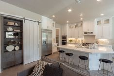 White kitchen with sliding barn door and hidden desk and bookshelf in EVRGRN Rok gray
