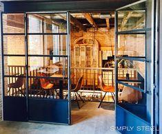Blanke stalen deuren in industrieel interieur. Een vintage horeca interieur waar iedereen zich thuis voelt. De eiken gebinten, bakstenen wand, betonnen vloer zijn stoer en warm tegelijk. #simplysteel #industrialstyle