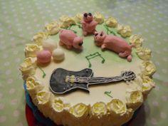 Janin kakku - Tämän kakun tein yhdessä lasten kanssa, tytöt 5- ja 7-vuotta tekivät possut ja äiti muut jutut. Mieheni soittaa kitaraa ja on ollut teurastamolla töissä, siksi siis kakussa possuja ja kitara. Kitara on tehty Janin oman kitaran malllin mukaan. Reunaruusuihin kokeilin ekan kerran terälehti-tyllaa.