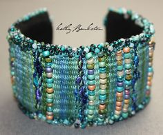 Intricately hand woven and beaded cuff bracelet. Beautiful shades of teal-blue, green, and purple, hand-dyed mulberry silk are woven with glass seed beads to create this richly colorful bracelet. Comp