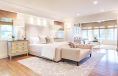 Tyra Banks' neutral bedroom with a patterned rug and high ceilings