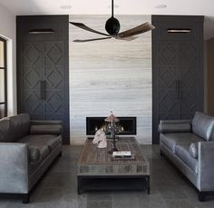 Contemporary living room features a ceiling fan over gunmetal gray leather sofas with matching bolster pillows facing each other across from a wood and iron coffee table atop gray tiled floors.