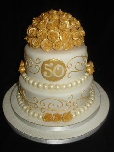 Golden (50th) Wedding Anniversary Fondant Cake - (Sep 2013) This is the 3rd time I've made this cake, but made it into a Anniversary cake as per the clients request. Was a bit worried about making everything gold, but I think it turned out beautifully. All the roses are made from flowerpaste/gumpaste and they've been painted with Gold Lustre Dust. Hope you enjoy. xMCx