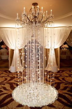 Delicate garlands of white orchids and crystals were suspended from glittering chandeliers for an extravagant look. #receptiondecor Photography: Bob & Dawn Davis Photography. Read More: https://www.insideweddings.com/weddings/vibrant-fall-wedding-with-lush-flowers-in-chicago-illinois/587/