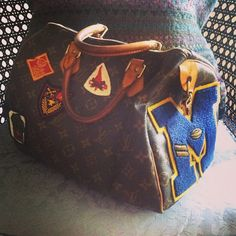 my mom's LV speedy bag adorned with  my stepfather's old high school football letters and his boy scout patches.