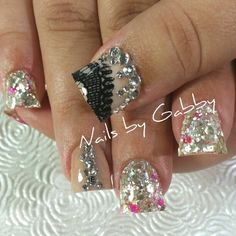 Acrylic nails with lace, bling, and glitter.