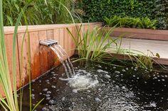 Strakke vijver met waterspuwers en vlonder in Nunspeet