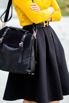 Yellow Cardigan Tucked Into Black Pleated Swing Skirt with Hermes Logo Belt