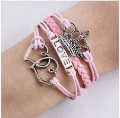"""Be queen when rocking this pink wrap bracelet. Complete with a love charm, dainty crown and double hearts, check off all the feminine things a queen could ever need in a bracelet.  Size: 6"""" long with a 2"""" extender to fit most wrists Materials: Wax cord, faux leather, zinc alloy Clasp: Toggle clasp for ease of use and lobster clasp for easy extension."""