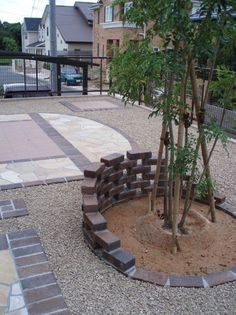 土間デザインでみせるドライガーデンのご提案。自然石、タイル、レンガ、砂利で表情豊かにお庭を演出。高さを出すためシマトネリコを植え、足もとにレンガのウォールを造作。