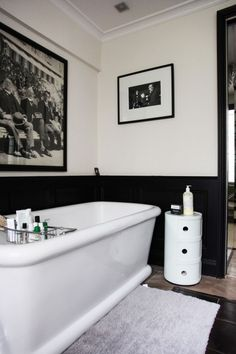 traditional bathroom in black & white & with a sense of humour. black wainscoting, white tub, Kartel storage unit with some very serious looking B & W photos