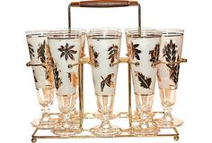 """Pilsners w/ caddy. Glasses, 8.25"""" high by 2.75"""" across.  Caddy 13"""" length by 7"""" width by 12"""" high."""