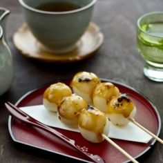 Warm soft grilled mochi ball covered in a sweet soy sauce, a traditional Japanese sweet.