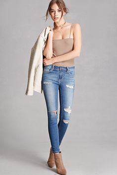 A pair of skinny jeans featuring a distressed style, a rip at the knees, a five-pocket construction, a low-rise, and a zip fly closure. This is an independent brand and not a Forever 21 branded item.
