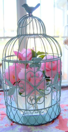 bird cage filled with flowers from the yard. inexpensive centerpiece