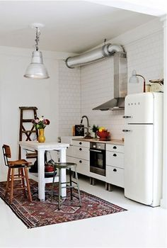12 Kitchens & Dining Rooms Made Cozy With Kilims: The family who lives in this home featured in Elle Interior Sweden owns vintage shop Dusty Deco in Stockholm. The somewhat formal kilim pulls together the room, with its mismatched chairs and retro Smeg fridge.