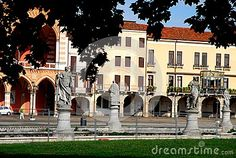 Photo made in Prato della Valle in Padua in Veneto (Italy). In the picture with frame of leaves and green grass, taken from the inside of the island Memmia, you see some statues surrounding the island perimeter, some buildings that are part of the corolla of buildings surrounding the large square seats to west and a small portion of blue sky dl over the houses and among the leaves.