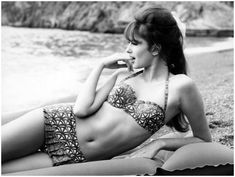 Vintage beach style. A woman poses on a beach wearing a printed balconette bikini. Photo via Getty Images.