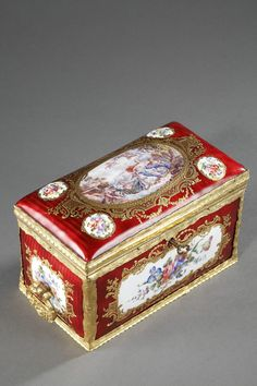 A rectangular red enamel casket with gilt bronze frame, very finely chiselled with scrolling foliate. The body of the box is decorated with medallions illustrating polychromatic bunches of f