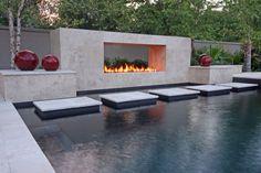 Cheminée au design contemporain qui apporte une touche luxe à cette belle piscine design