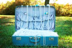 Shutterbugg01 - Suitcase Setup    I used natural lighting in open shade and I just added a couple of pillows with a strip of fur in the suitcase. Draped some pearls, added some little fake blue birds and an iddy biddy crown. Underneath the fur is actually a very stiff piece of cardboard the length of the suitcase that is there to prevent baby from sinking into the softness of the pillows. I used my Canon 60D an my 50mm 1.8 for the pic. It was soooo difficult to get this shot. I am totally…