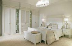 chambre à coucher blanche aménagée avec un grand dressing encastré dans le mur