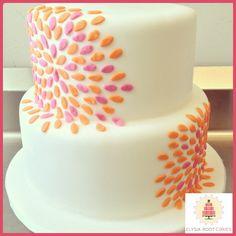 2 tier wedding cake with bright orange and pink starburst design based on the couple's wedding invitation