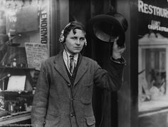 Eighteen year old inventor, H. Day wearing headphones attached to a wireless under his top hat, 1922.