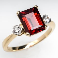 Malaya Garnet Engagement Ring Bezel Set Diamond Accents 18K Gold - This beautiful engagement ring is centered with an emerald cut 2.65 carat Malaya garnet. Each shoulder is set with a round brilliant cut diamond in a platinum bezel. The ring is crafted of solid 18k yellow gold and is in excellent condition.