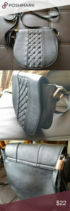 "Shoulder bag by Orange Caramel Sporty mid sized black vegan leather saddlebag with gold tone rivets detailing flap, magnetic closure and black tassel bag charm. Adjustable to wear as shoulder bag or crossbody, strap measures from 21""drop to 24"". Bag tapers slightly from 10.5"" wide at the top,  and is 9"" tall from center bottom to top. Bottom of the purse measures 4"" deep. Some wear on the strap, none on the body, lining is intact. Excellent used condition. Orange Caramel Bags"