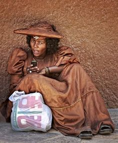 Candid street shot of Herero tribe girl in specific for that tribe Victorian dress and hat (which is strong contrast to coexisting Himba women who are naked and smeared with ochra&butter). I was spellbound by neatly matching colors, style and beauty of girl, as well as the combination of old and new times. Northern Namibia.