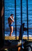 Banhista fala no celular enquanto se bronzear na praia do Perequê em Ilhabela, Brasil, em uma manhã ensolarada.