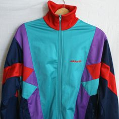 """100% GENUINE ITEM, IT FEATURES THE OLD ADIDAS LABEL FROM 90's. FULL ZIP / 2 ZIPPED POCKETS / MULTI-COLOR DESIGN / TREFOIL & 'adidas'. zip (front) length: 28.4 in = 72 cm. SIZE LABEL STATES D/I/CH 6 FR 180, WHEN FLAT CHEST MEASURES 44"""". 