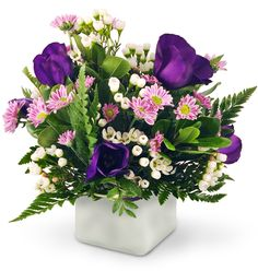 Send someone your sweetest thoughts drifting on a delightful summer  breeze with our Wishes and Kisses bouquet! Perfect pinks, pleasing  purples and polka-dots of white all dance in a meadow of lush green.  This light-hearted arrangement is a wonderful way to make someone's day! Delicate lisianthus, miniature daisies, and waxflowers are beautifully  arranged in a frosted glass cube and accented with leatherleaf and  pittosporum.