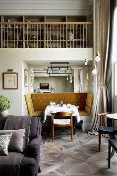 A stylish small flat with open Plan Living room/Dining Room With Inbuilt Banquette, Seating mezzanine bookshelves and pendant lighting, mustard velvet seating. Small space ideas.