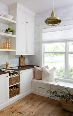 In an well styled kitchen pantry, white floating shelves are mounted against a honed gray marble subway backsplash between stacked white cabinets accented with brass knobs.
