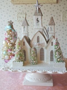 RESERVED for TONYA - This lovely cathedral is reminiscent of the old style, Putz pieces. Glistening white walls and a glittered roof add lots of sparkle and creates a fantasy inspired piece. There are faux windows, a glittered northern star at the top of the steeple, and a balconette featuring faux pink pearl garland and sweet pink and cream paper roses. Three pale green bottle brush trees are adorned with faux pearls, glass beads and more creamy roses with pale pink centers. This is an…