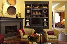 Like the black fireplace and customized bookcase against the yellow walls, with the red accents. (Actually, the room also has a red sofa and red in other upholstery.) Nice way to display collection of tribal accessories.