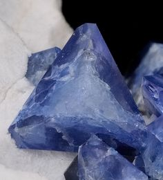 Benitoite crystal on unusal field of snowy white Natrolite. Benitoite is a blue barium titanium silicate mineral, found in hydrothermally altered serpentinite. It is the CA state gemstone.