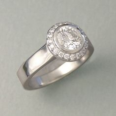 Engagement Ring 1-3: Round cut diamond full bezel set in platinum surrounded by small bead set diamonds. Handmade by Bill Cronin in Boulder, CO.