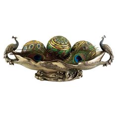 A chic addition to your centerpiece or mantel, this lovely hand-finished bowl showcases 2 peacock accents and a scrolling garland base.