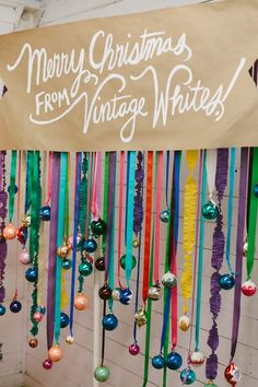 (photo booth) brightly colored ribbon and ornaments on a PVC frame to create a super fun and festive backdrop, and scattered neon pom-poms all over a tree...