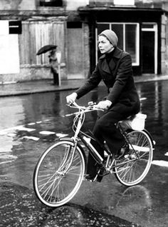 Ingrid Bergman on bicycle on a rainy day.