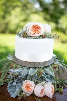 simple white cake with garden rose topper