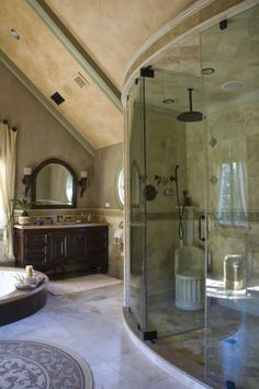 Beautiful Mediterranean inspired bathroom with marble tiling and a spectacular curved glass-fronted shower