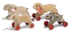 FOUR STEIFF RUNNING RABBITS, THREE ON WHEELS, one white mohair without wheels, (1314), brown and black glass eyes, pink stitching, inoperative squeaker and FF button, 1920s --9½in. (24cm.) long; one with grey-tipped and white mohair on eccentric wheels, (1312 ex), FF button and yellow cloth tag, 1930s --7in. (18cm.) long; and two others on red wooden eccentric wheels, both with FF buttons --9¼in. (23.5cm.) and 7in. (18cm.) long (some wear and fading)