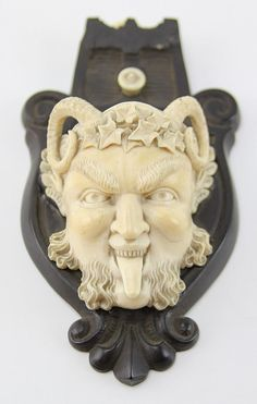 """ANTIQUE IVORY SATYR ATTACHED TO WOODEN PLAQUE Antique ivory carving of a satyr's head sticking his tongue out and wearing an ivy crown. Head is attached to a dark wooden plaque, surrounded by a simple design. A small ivory loop is attached to the top of the plaque for displaying purposes. Weight: 181.5g (including plaque) Size: 6.5 x 3.5"""" (including plaque)"""