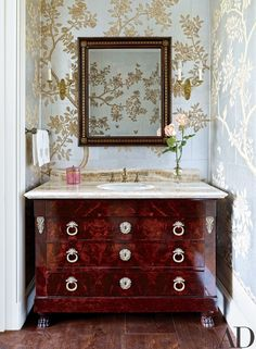 Gracie wallpaper lines a powder room; the vanity was made from a Directoire commode.